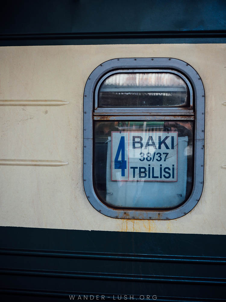 A train with a sign reading Baku Tbilisi in the window.