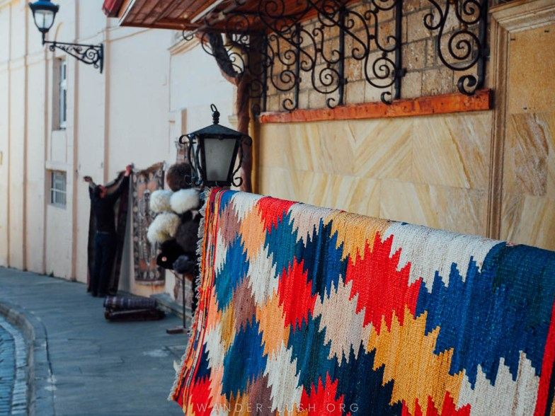 A man hangs colourful rugs outside his shop in Baku.