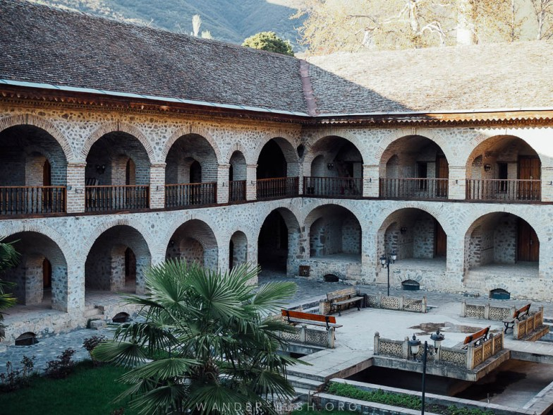 A huge stone building with multiple arches and a central courtyard.