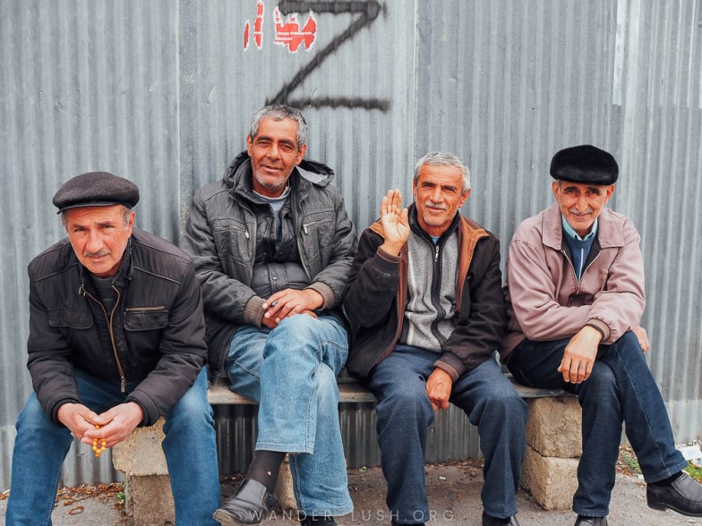 Four men in Azerbaijan smile and wave for the camera.
