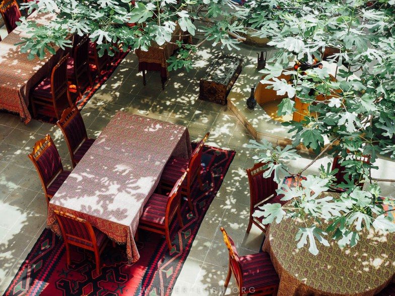Looking down through the trees on dining tables with printed tablecloths.