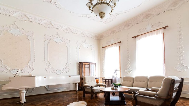 An old-style living room with white moulded walls and a white grand piano.
