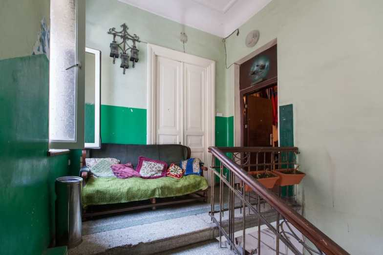 An old staircase with wooden banisters leads to a landing with a green sofa.
