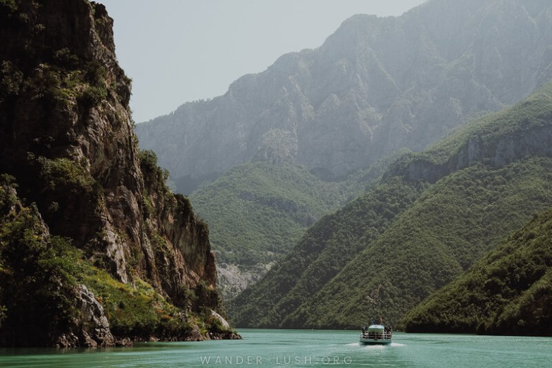 A boat on a lake surrounded by high mountains.