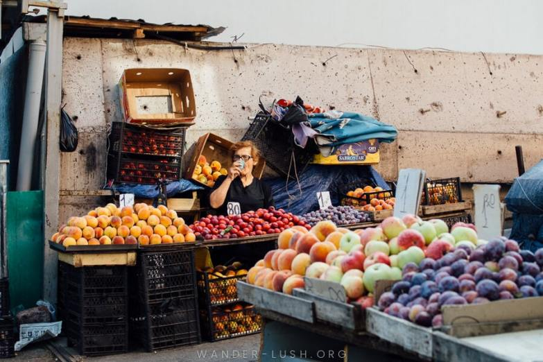 A female vendor sits at a table in front of piles of fruit.