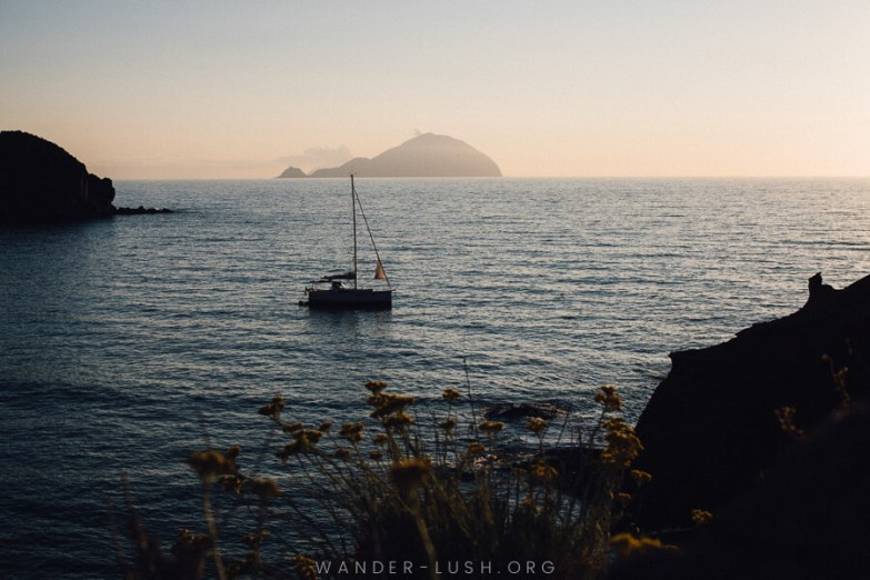 Dusk over the sea, with an island in the background and a single sail boat.