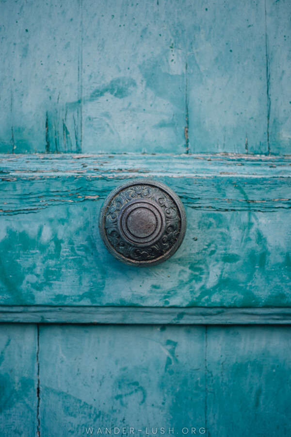 Close up of a weathered blue door with a beautiful metal handle.
