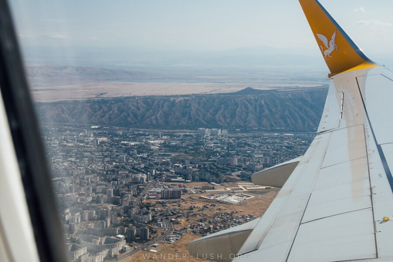 View of mountains and a city from an airplane window with the wing of the plane in the foreground.