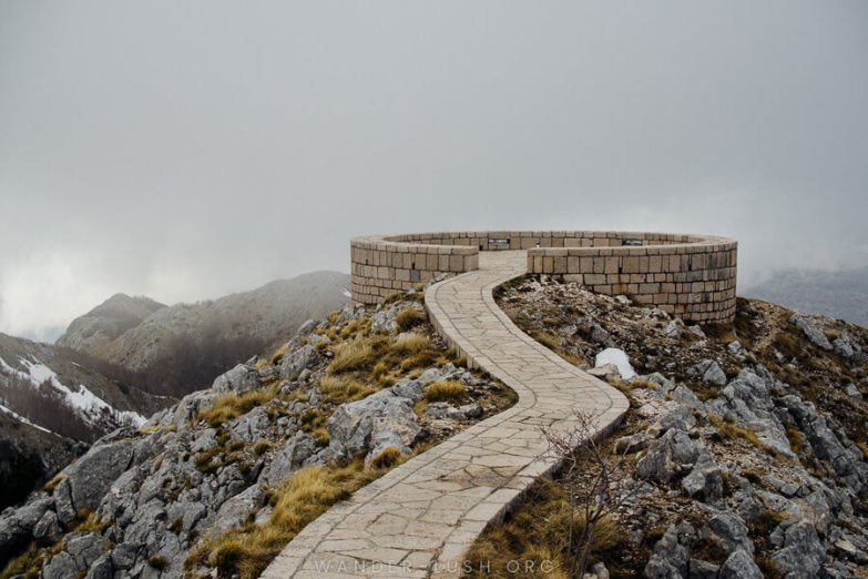 A stone lookout platform with thick grey clouds in the backdrop.