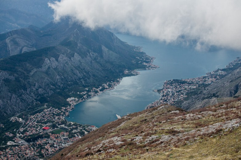 Driving in Montenegro, looking down on a narrow bay with thick clouds overhead.