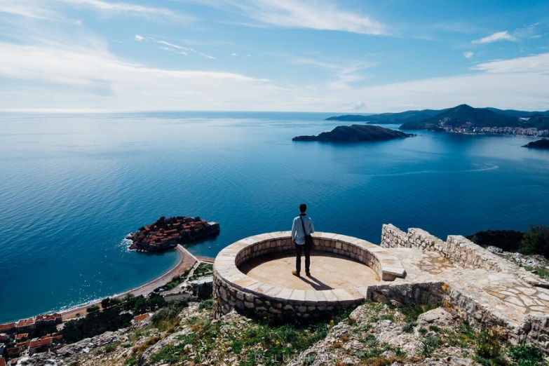 A person stands on a round viewing platform overlooking the ocean and a small island.
