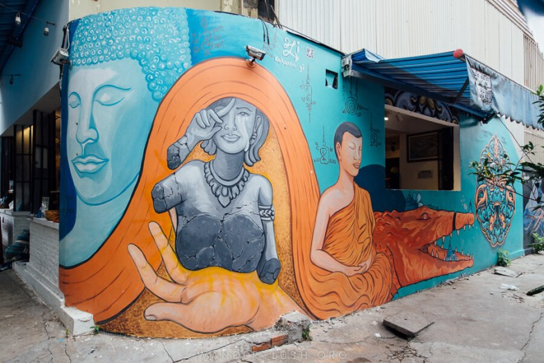 A large wall mural depicting Buddhist symbols in blue and orange paint.