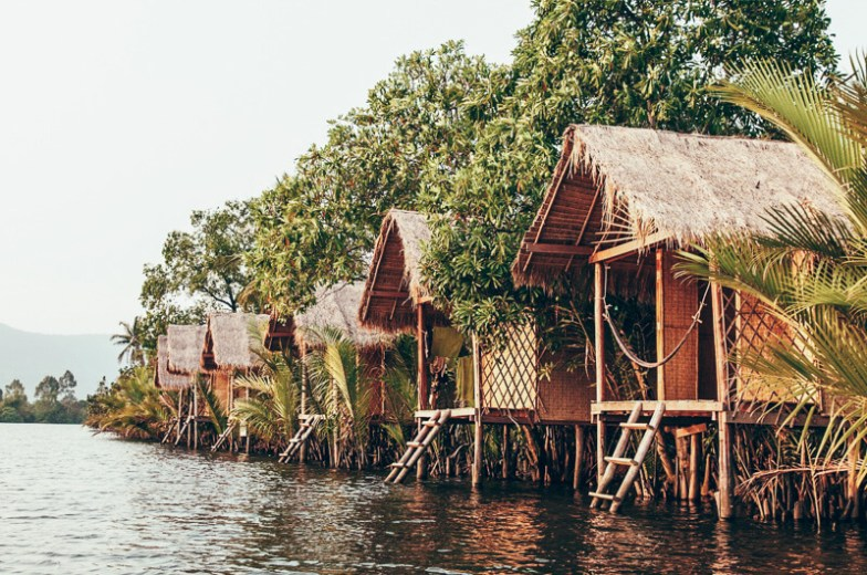 A row of bamboo bungalows on the edge of the river in Kampot, Cambodia.