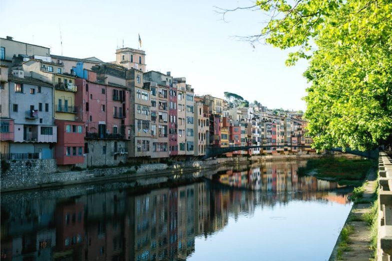 A row of colourful houses overhanging a river.