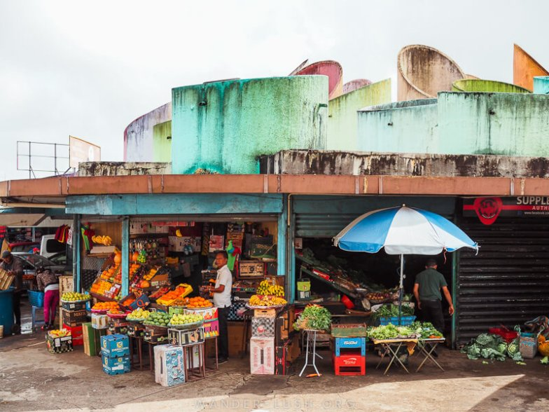 A man looks out from his fruit stall at a colourful marketplace in Mauritius.
