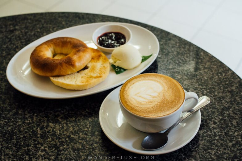A bagel served with cream cheese and jam, and a cup of coffee.