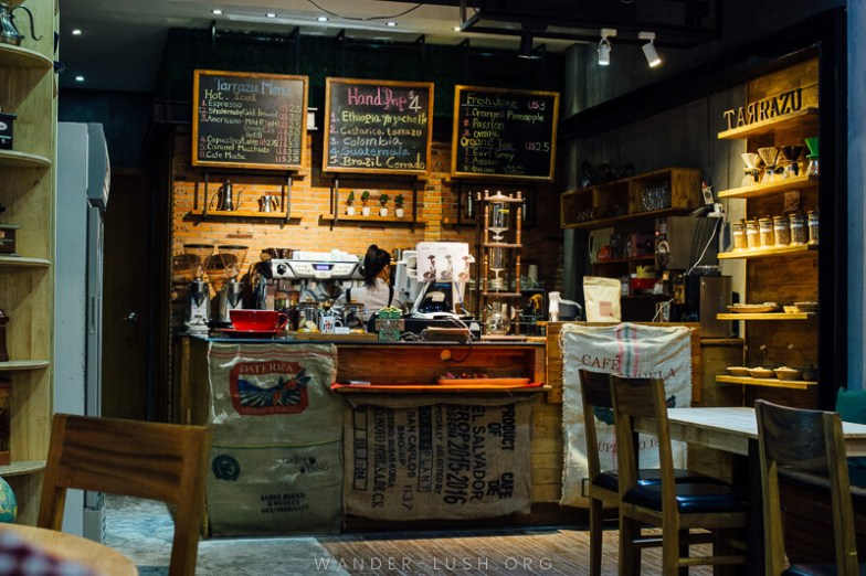 A dark and cluttered cafe decorated with coffee sacks.