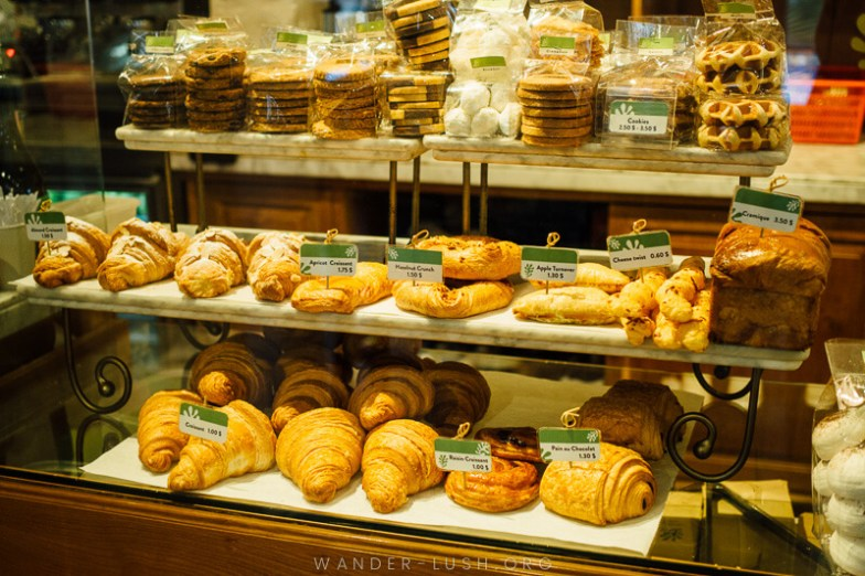 A cafe cabinet filled with croissants, cookies and baked goods.