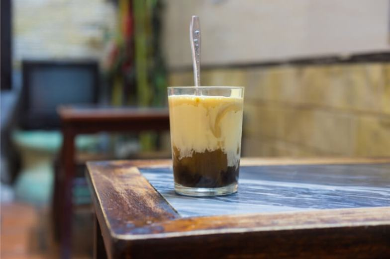 A glass of iced coffee on a table.