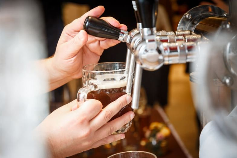 A person pulls a glass of beer.