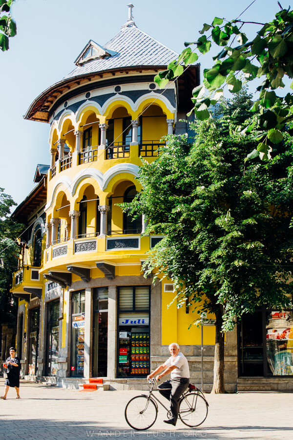 A man rides a bicycle in front of a yellow building in Korca, Albania.
