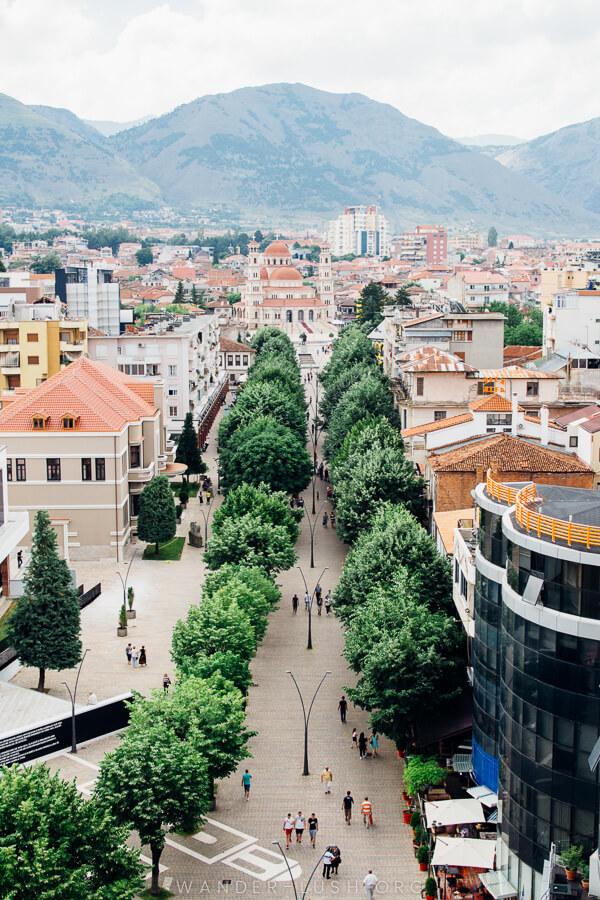 A tree-lined pedestrian street in Korca, Albania.