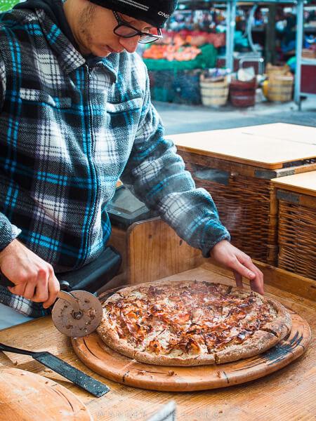 A man cuts a pizza at a market in Ljubljana.