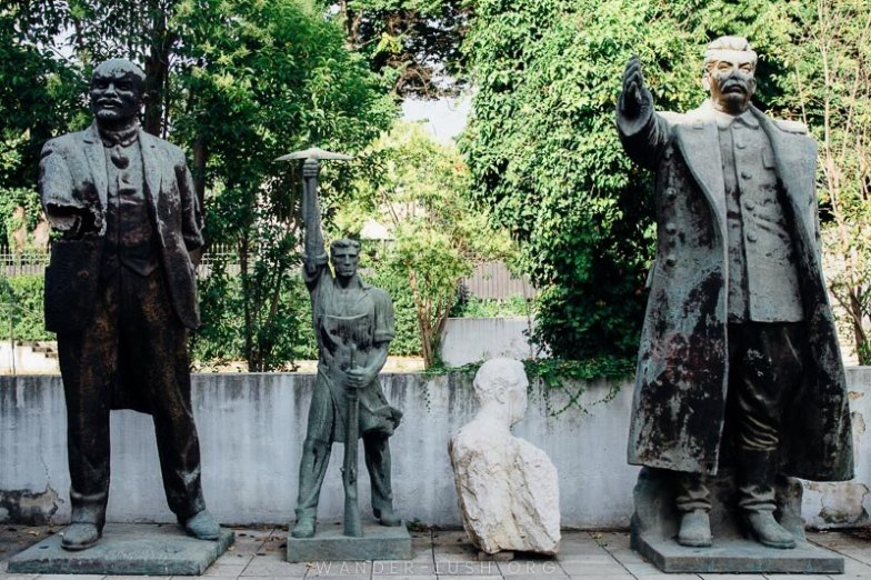 Four damaged statues in a garden.