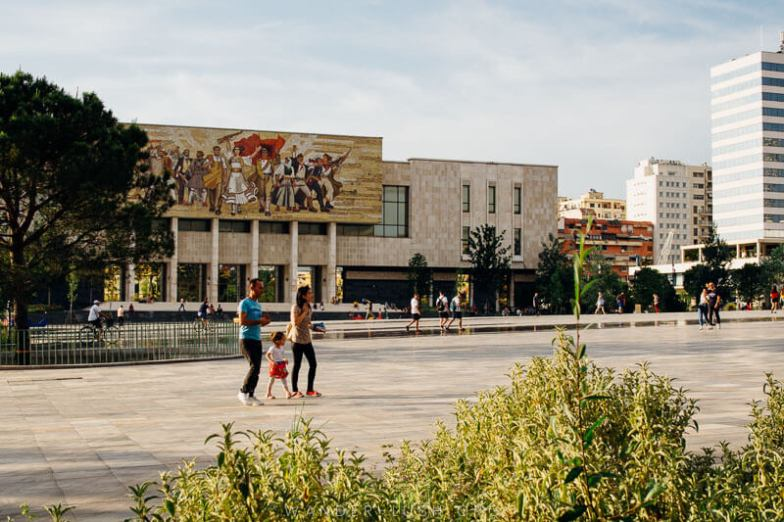 A family walks across a square in Tirana, Albania.