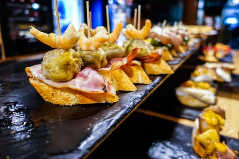 Small pieces of bread topped with ham, pickles and other ingredients.