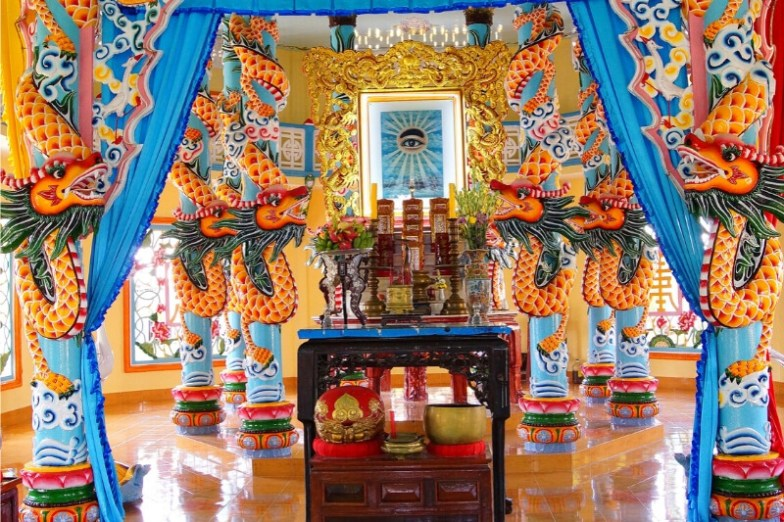 Inside a colourful temple with painted pillars and a wooden shrine at the centre.