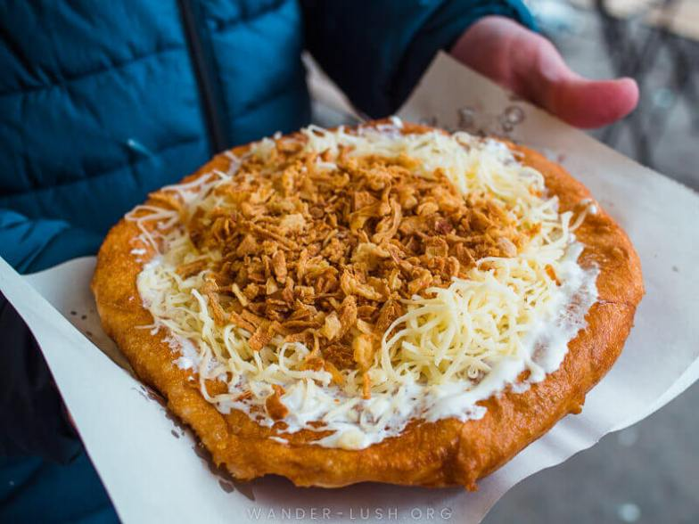 Langos, fried dough topped with sour cream, cheese and onions.