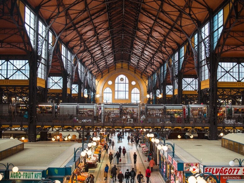 The interior of a busy market hall with a steel roof.