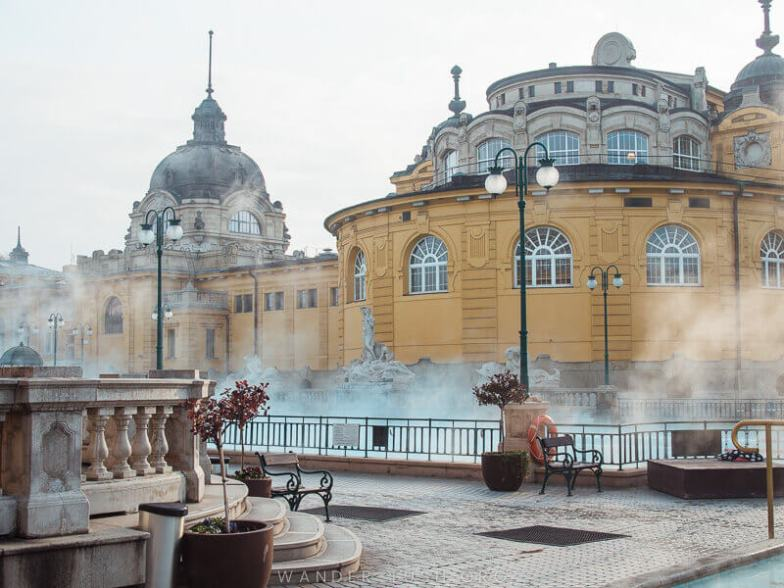 A yellow facades surrounded by steaming hot pools.