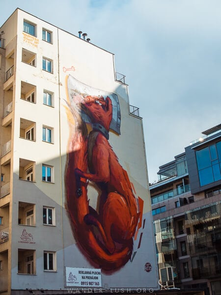 A tall apartment building with a mural depicting a fox.