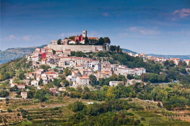 A beautiful white city and fortified castle atop a green hill in Istria, Croatia.