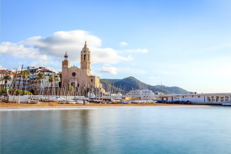 A beautiful church visible on the short surrounded by boats and a clear sea in Spain.