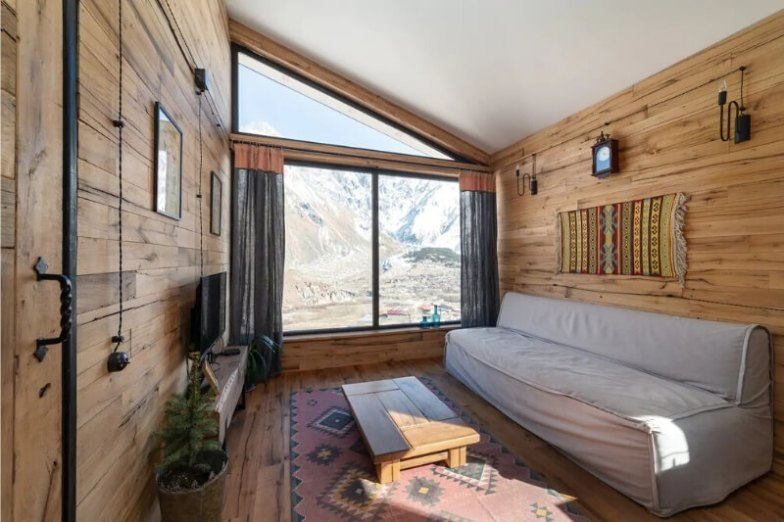 A modern wood cabin with floor rugs and wood on the walls.