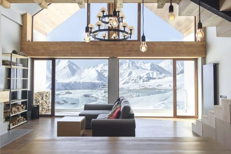 An ultra-modern mountain chalet with a fireplace and widows looking out to snow-capped mountains.