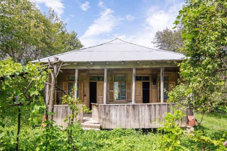 A historic wooden house with a verandah and tin roof.