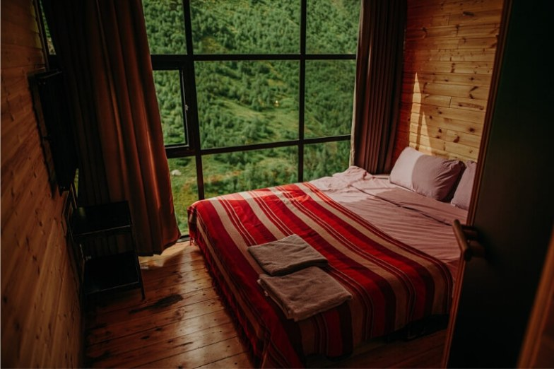 A small wood-paneled room with a cosy bed and windows overlooking a green forest.