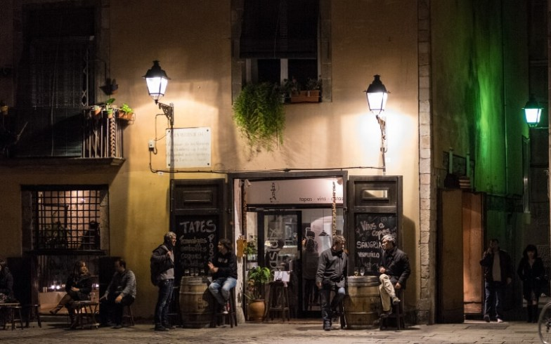 People gather outside a cafe at night.