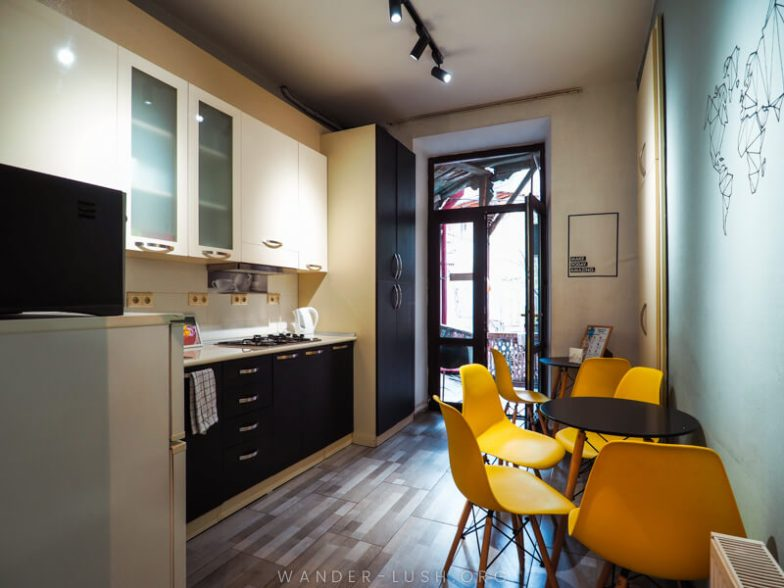 A kitchen with yellow chairs and tables.