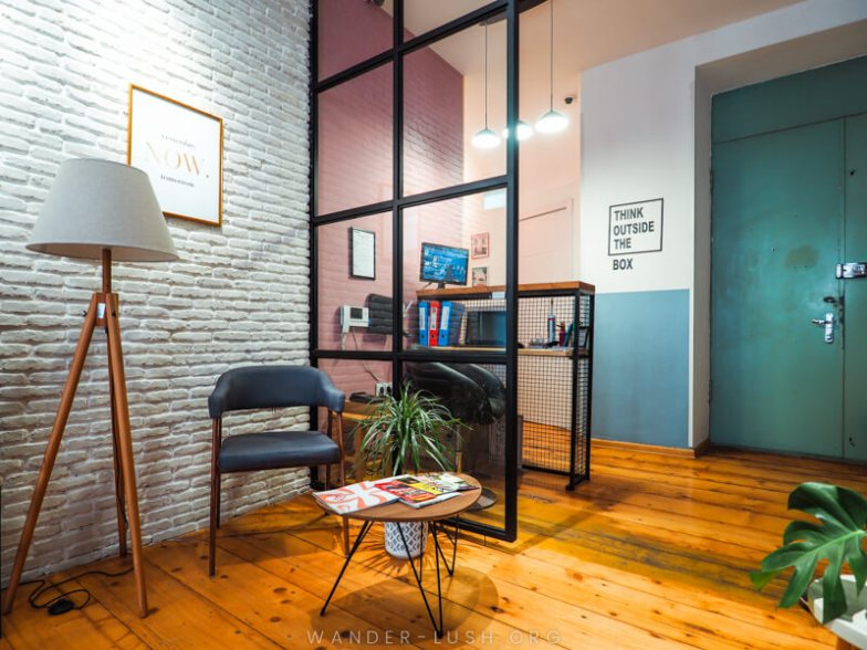 A modern hostel room with brick walls and comfortable furnishings.