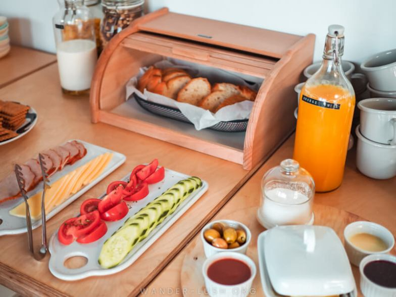 Fresh bread and sliced vegetables on a wooden table.