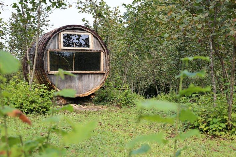 A barrel transformed into a sleeping pod in a grassy field in Georgia.