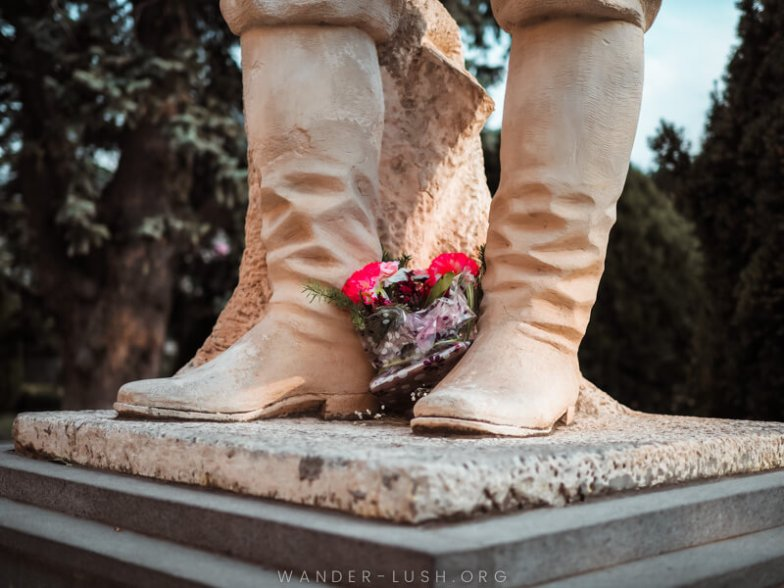 A bunch of flowers lay at the feet of a stone statue.
