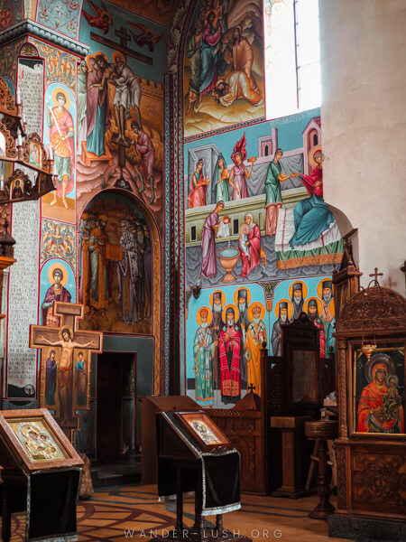 Colourful murals decorate the interior of an Orthodox church.