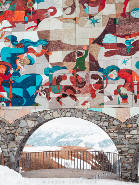 A colourful mosaic and a stone archway.