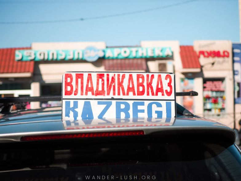A taxi with a sign reading 'Kazbegi' on its roof.